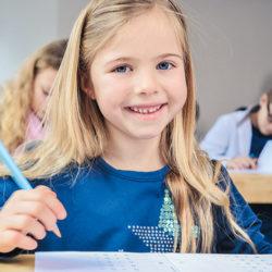 blondes kleines Mädchen, lächelnd, Stift haltend
